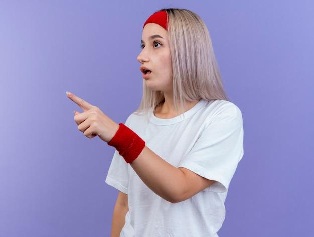 Zaskoczona młoda sportowa kobieta z szelkami, nosząca opaskę i opaski na nadgarstek, wygląda i wskazuje na bok na białym tle na fioletowej ścianie