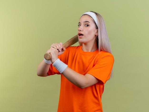 Zaskoczona młoda wysportowana dziewczyna rasy kaukaskiej z szelkami, nosząca opaskę na głowę i nadgarstki, trzymająca kij bejsbolowy