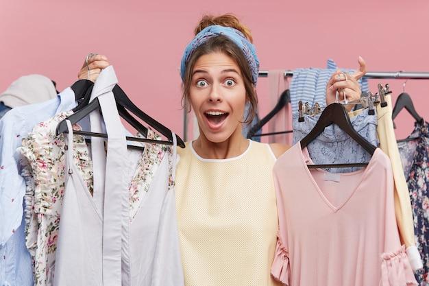 Zaskoczona modelka trzymająca w dłoniach wiele wieszaków z ubraniami, zamierzająca założyć je w przymierzalni, nie wiedząc, co najpierw spróbować. zszokowana piękna kobieta robi zakupy w domu towarowym