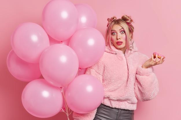 Zaskoczona modna kobieta ubrana w stylowe ciuchy robi fryzurę i nakłada makijaż na specjalne okazje trzyma przeszklony pączek pęk napompowanych balonów cieszy się wakacyjnymi pozami w domu