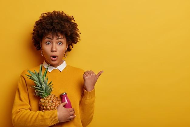 Zaskoczona, pełna emocji kobieta o włosach afro trzyma świeżego ananasa i butelkę różowego smoothie