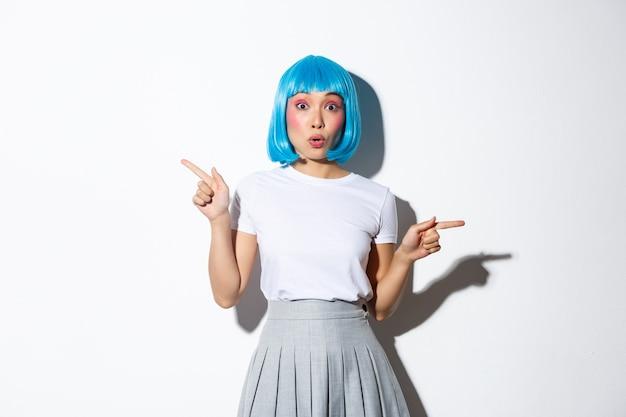 Zaskoczona piękna azjatka w niebieskiej krótkiej peruce, stojąca i wskazująca palcami w bok ze zdumieniem.