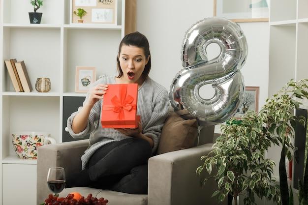 Zaskoczona piękna dziewczyna na szczęśliwy dzień kobiet trzymająca i patrząca na teraźniejszość siedząca na fotelu w salonie
