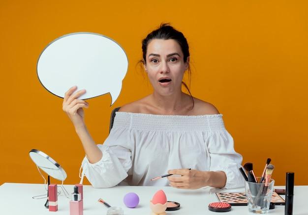 Zaskoczona piękna dziewczyna siedzi przy stole z narzędziami do makijażu trzyma bańkę czat i pędzel do makijażu na białym tle na pomarańczowej ścianie