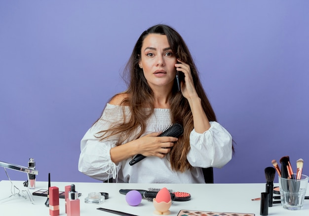 Zaskoczona piękna dziewczyna siedzi przy stole z narzędziami do makijażu trzyma grzebień do włosów rozmawia przez telefon na białym tle na fioletowej ścianie
