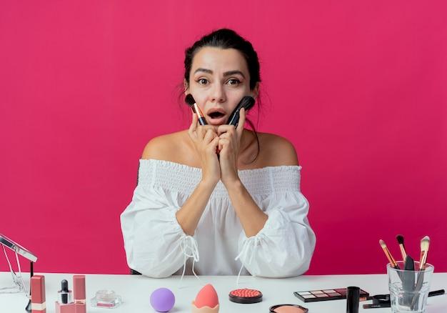 Zaskoczona piękna dziewczyna siedzi przy stole z narzędziami do makijażu trzyma i nakłada pędzle do makijażu twarzy na różowej ścianie