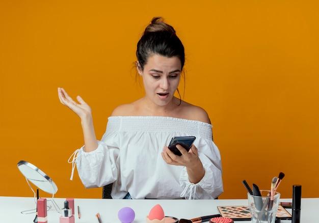 Zaskoczona piękna dziewczyna siedzi przy stole z narzędziami do makijażu trzyma i patrzy na telefon na białym tle na pomarańczowej ścianie
