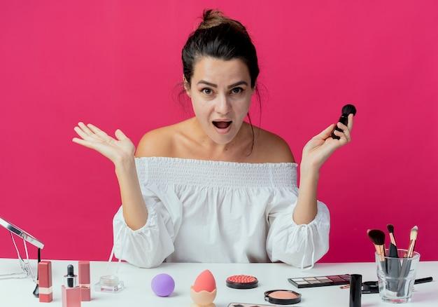 Zaskoczona piękna dziewczyna siedzi przy stole z narzędziami do makijażu trzyma pędzel do makijażu, podnosząc ręce na białym tle na różowej ścianie