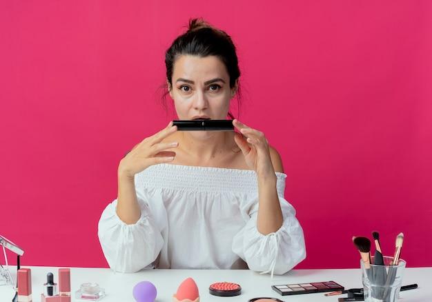 Zaskoczona piękna dziewczyna siedzi przy stole z narzędziami do makijażu trzyma tusz do rzęs na białym tle na różowej ścianie