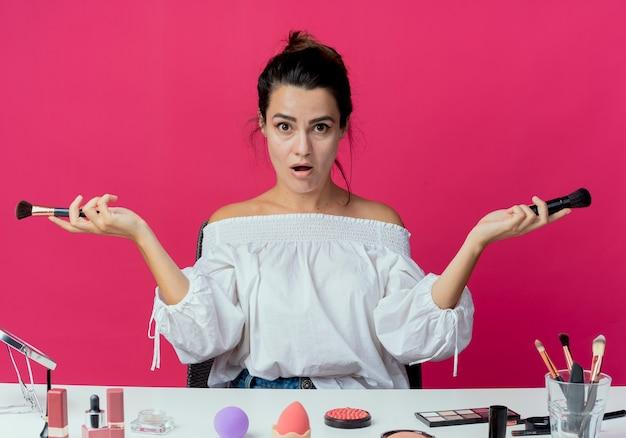 Zaskoczona piękna dziewczyna siedzi przy stole z narzędziami do makijażu, trzymając pędzle do makijażu na różowej ścianie