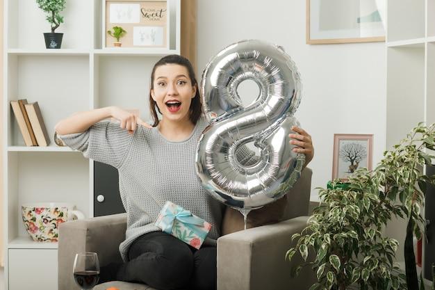 Zaskoczona piękna dziewczyna trzyma szczęśliwy dzień kobiet i wskazuje na balon numer osiem, siedząc na fotelu w salonie
