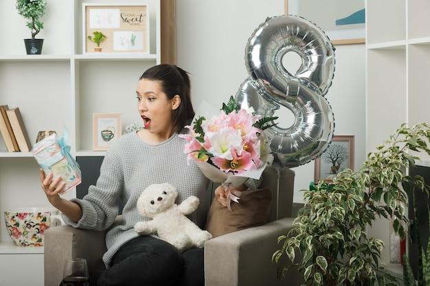 Zaskoczona piękna dziewczyna w szczęśliwy dzień kobiet trzyma bukiet, patrząc na prezent w dłoni, siedząc na fotelu w salonie