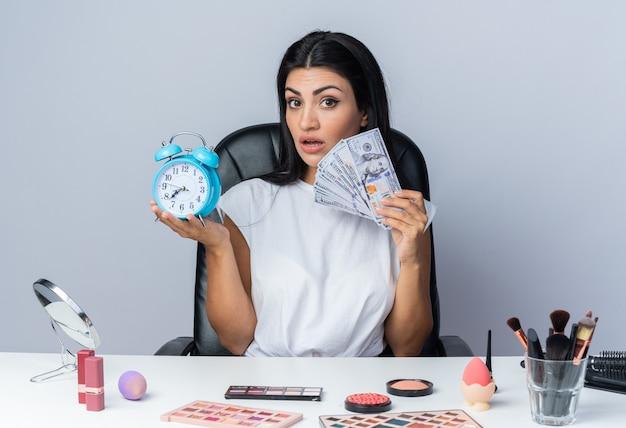 Zaskoczona piękna kobieta siedzi przy stole z narzędziami do makijażu, trzymając budzik z gotówką