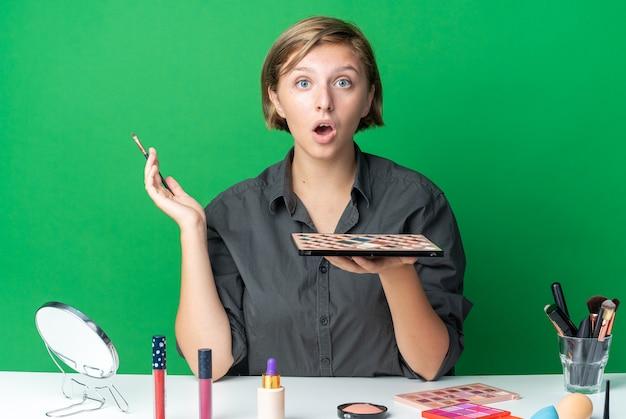 Zaskoczona piękna kobieta siedzi przy stole z narzędziami do makijażu, trzymając paletę cieni do powiek z pędzlem do makijażu