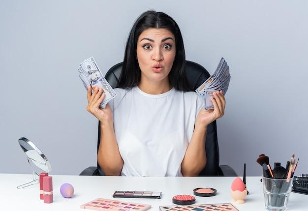 Zaskoczona piękna kobieta siedzi przy stole z narzędziami do makijażu trzymającymi gotówkę
