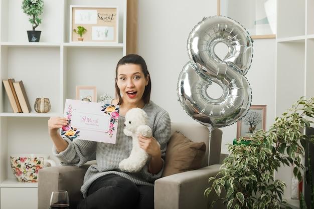 Zaskoczona piękna kobieta w szczęśliwy dzień kobiet trzymająca pocztówkę z misiem siedzącym na fotelu w salonie