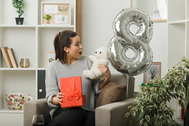 Zaskoczona piękna kobieta w szczęśliwy dzień kobiet trzymająca prezent i patrząca na misia w dłoni siedzącego na fotelu w salonie