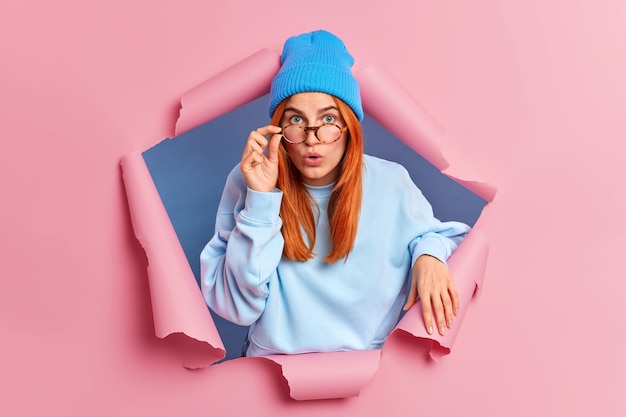 Zaskoczona piękna kobieta z naturalnymi rudymi włosami trzyma rękę na krawędzi okularów, wpatruje się w oszołomienie, gdy słyszy coś szokującego w niebieskim ubraniu.