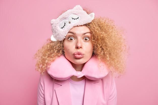 Zaskoczona piękna kobieta z założonymi ustami chce cię pocałować, nosi maskę do spania i poduszkę na kark, aby wygodnie spać, ubrana w eleganckie ubrania odizolowane na różowej ścianie. koncepcja odpoczynku.