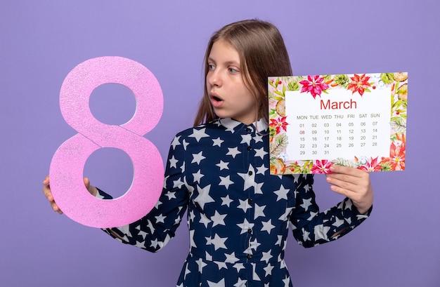 Zaskoczona piękna mała dziewczynka na szczęśliwy dzień kobiet trzymająca kalendarz patrząc na numer osiem w dłoni