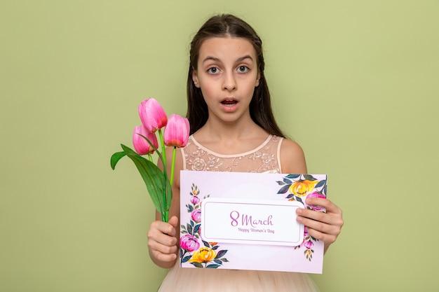 Zaskoczona piękna mała dziewczynka na szczęśliwy dzień kobiet trzymająca kwiaty z kartką z życzeniami