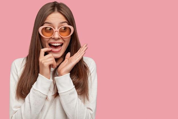 Zaskoczona piękna młoda kobieta o ciemnych włosach, nosi modne duże okulary przeciwsłoneczne, szeroko uśmiecha się do aparatu