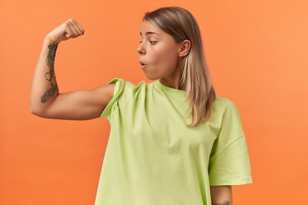 Zaskoczona piękna młoda kobieta w żółtej koszulce pokazująca mięśnie bicepsów i patrząca na nią odizolowana od pomarańczowej ściany