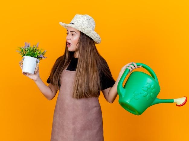 Zaskoczona piękna ogrodniczka w mundurze i kapeluszu ogrodniczym, trzymając konewkę i patrząc na kwiat w doniczce w dłoni na białym tle na pomarańczowym tle