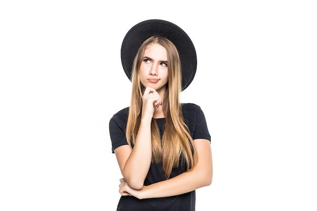 Zaskoczona poczęta dziewczyna w czarne ubrania i kapelusz na białym tle