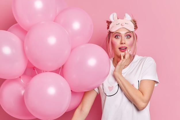 Zaskoczona, pod wrażeniem młoda europejka z makijażem, nosi maskę do spania i casualową koszulkę, która trzyma napompowane balony świętuje urodziny