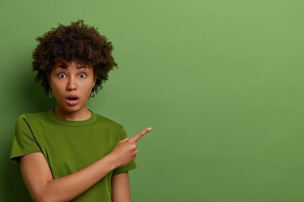 Zaskoczona, podekscytowana afroamerykanka ze zdziwieniem wskazuje palec wskazujący w bok, promuje nowy produkt, patrzy z szeroko otwartymi ustami na reklamę, nosi jasnozieloną koszulkę w jednym tonie z tłem