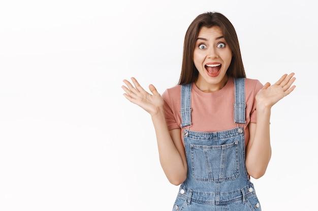 Zaskoczona, podekscytowana i wiwatująca ładna brunetka w ogrodniczkach, zapięcie koszulki dłonie zafascynowana i zdumiona, uśmiechnięta reakcja zdziwiona zabawnymi oszałamiającymi wiadomościami, białe tło