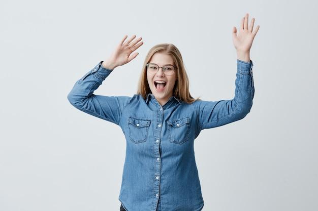 Zaskoczona podekscytowana kobieta o blond włosach i okularach patrzy, szeroko otwiera usta, podnosi ręce, jest zszokowana, patrząc na ceny w centrum handlowym, nie wierzy swoim oczom.