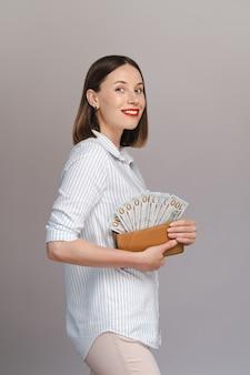 Zaskoczona podekscytowana młoda kobieta odizolowana nad szarą ścianą trzymająca pieniądze w portfelu