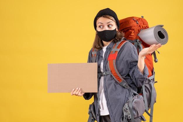 Zaskoczona podróżniczka z czarną maską i plecakiem trzymająca karton