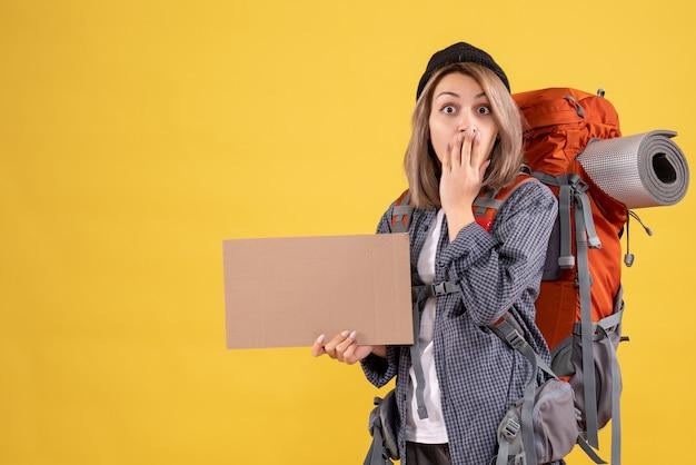 Zaskoczona podróżniczka z plecakiem trzymająca karton