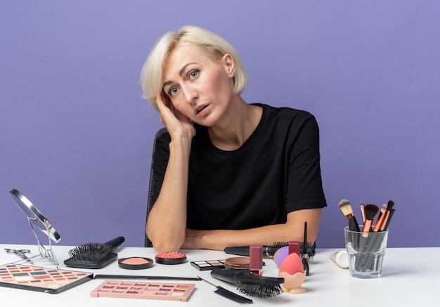 Zaskoczona przechylająca się głowa patrząc na kamery młoda piękna dziewczyna siedzi przy stole z narzędziami do makijażu, kładąc rękę na policzku na białym tle na niebieskim tle