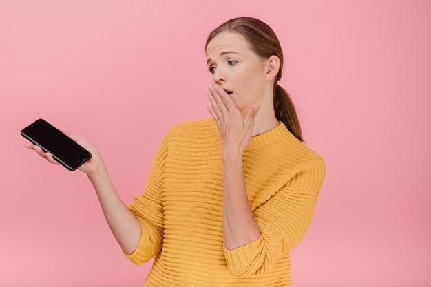 Zaskoczona, przestraszona i zdumiona atrakcyjna kobieta w żółtym swetrze ze zepsutym ekranem telefonu w dłoni