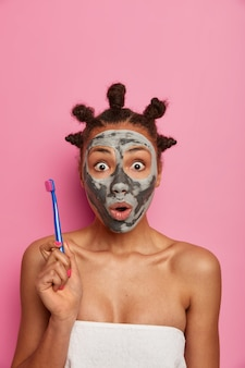 Zaskoczona przestraszona kobieta wpatruje się w zatkane oczy, trzyma szczoteczkę do zębów, idzie do czyszczenia zębów po zdjęciu maski upiększającej z twarzy, dba o urodę i higienę, nosi ręcznik kąpielowy na nagim ciele
