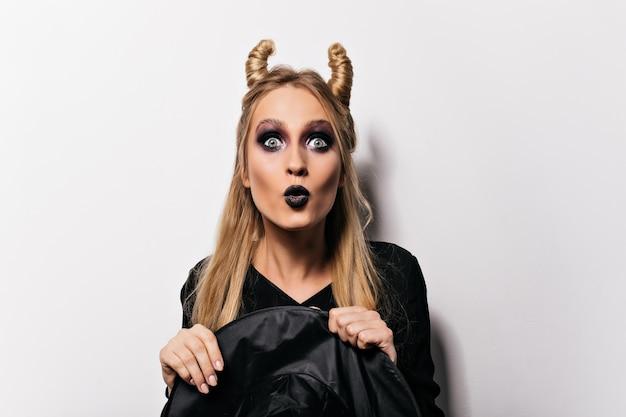 Zaskoczona przystojna dziewczyna w stroju czarownicy zdumiona modną damą świętującą halloween.