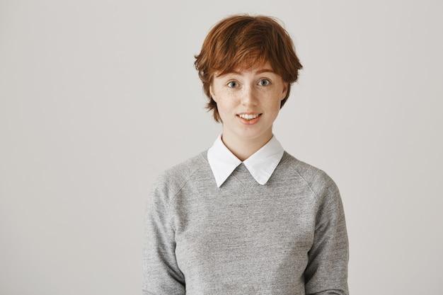 Zaskoczona ruda dziewczyna z krótką fryzurą, pozowanie na białej ścianie