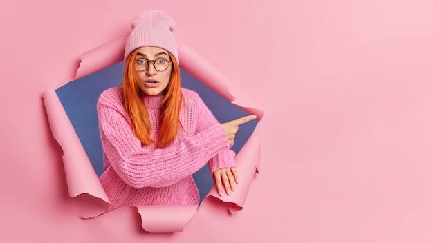 Zaskoczona rudowłosa kobieta czuje się zdumiona, wskazuje na miejsce, nosi dzianinową czapkę i sweter