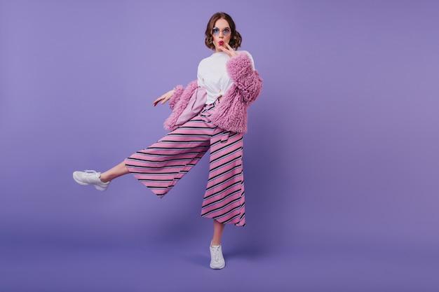 Zaskoczona śliczna dziewczyna w białych butach pozuje na fioletowej ścianie podczas wewnętrznej sesji zdjęciowej. pełnometrażowy portret zainteresowanej kręconej kobiety w różowych spodniach i eleganckiej futrzanej kurtce.