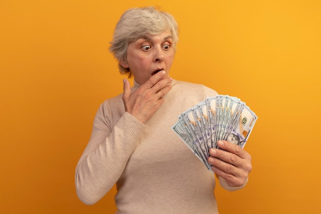 Zaskoczona stara kobieta w kremowym swetrze z golfem, trzymająca i patrząca na pieniądze trzymające rękę na ustach