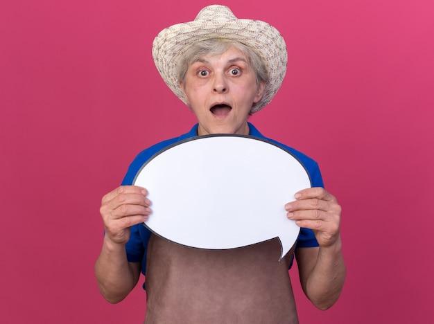 Zaskoczona starsza kobieta ogrodniczka w kapeluszu ogrodniczym trzymająca dymek na różowej ścianie z miejscem na kopię