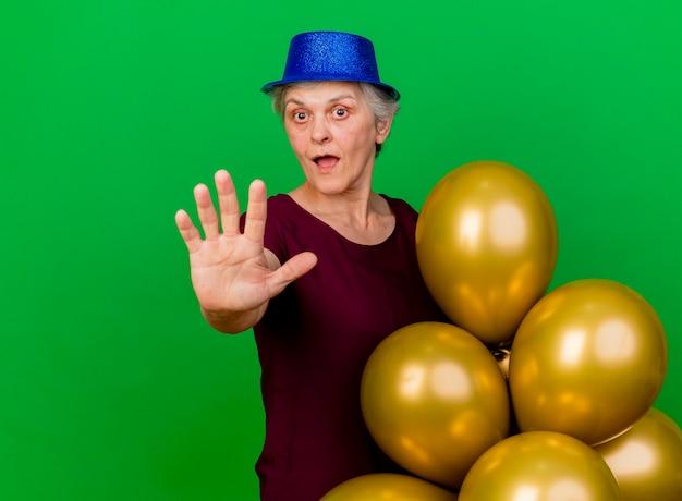 Zaskoczona starsza kobieta ubrana w imprezowy kapelusz stoi z balonami helowymi, wyciągając rękę na zielono