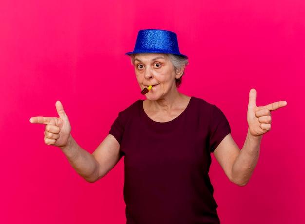 Zaskoczona starsza kobieta ubrana w imprezowy kapelusz wskazuje po bokach dmuchanie w gwizdek na różowo