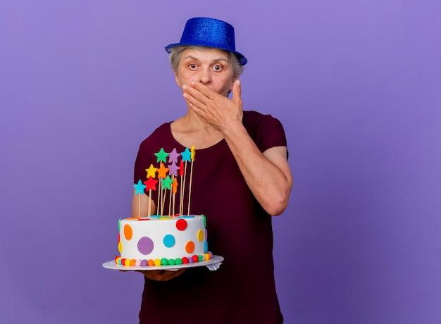 Zaskoczona starsza kobieta w kapeluszu imprezowym kładzie rękę na ustach i trzyma tort urodzinowy na fioletowej ścianie z miejsca na kopię