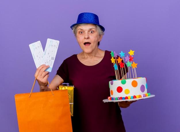 Zaskoczona starsza kobieta w kapeluszu imprezowym trzyma pudełko biletów lotniczych papierową torbę na zakupy i tort urodzinowy na białym tle na fioletowej ścianie z miejsca na kopię