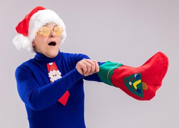 Zaskoczona starsza kobieta w okularach przeciwsłonecznych z czapką i krawatem świętego mikołaja wbija rękę w pończochę świąteczną na białym tle na białej ścianie z miejscem na kopię